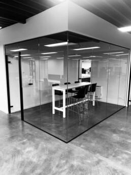 Glazen scheidingswand met kaderdeur in vergaderzaal