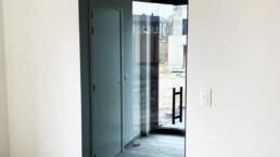 Pivoterende glazen deur met grijs glas