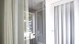 Glazen aanslagdeur met glazen wand